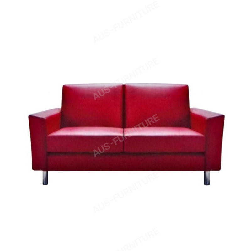 a red couch sitting in a room next to a wall