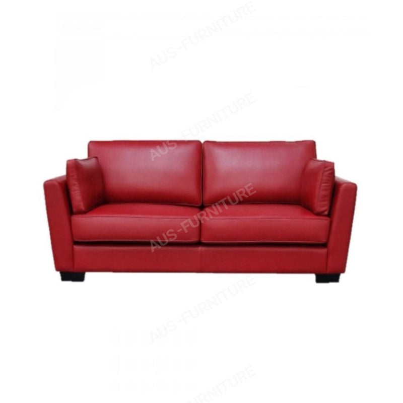 a red couch sitting on top of a white table