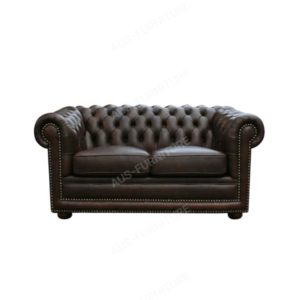a black leather couch with a cat sleeping on it