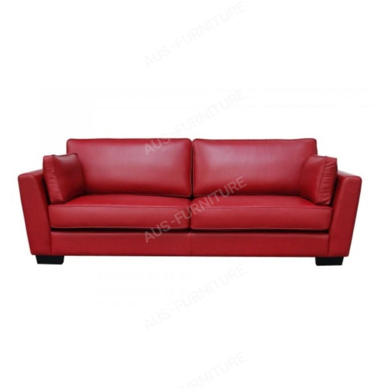 a red couch sitting on top of a white wall