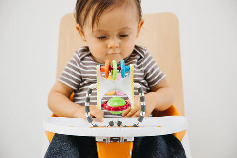 a baby in a high chair playing with  toy
