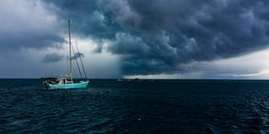 yacht sailing through a storm that is brewing across the ocean