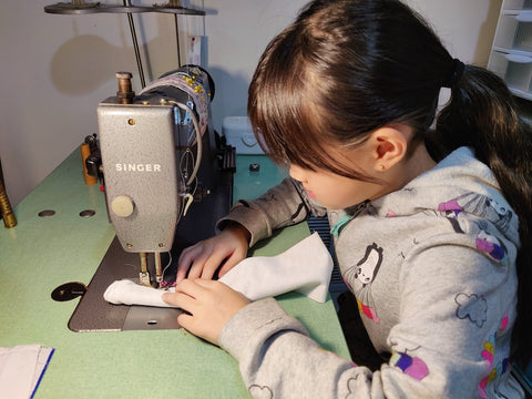 Lil lady sewing on industrial sewing machine