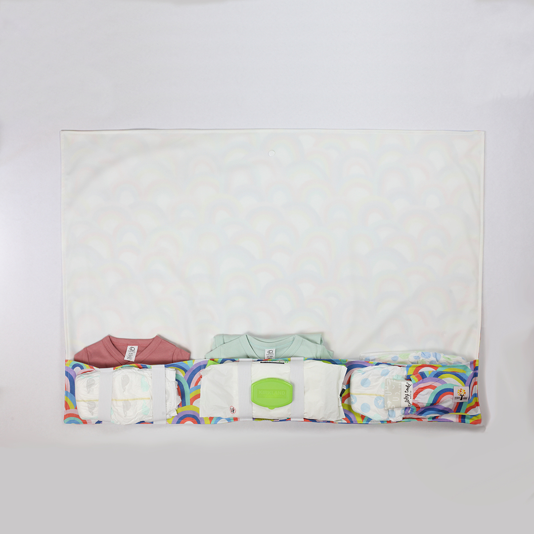 full body changing pad filled with onesies, diapers, ointment, and baby wipes