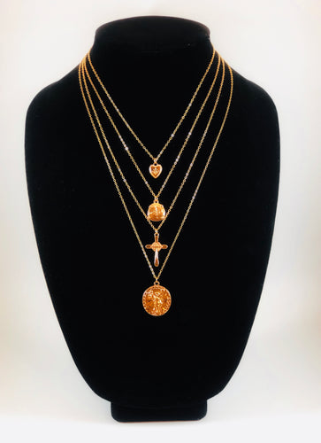 Set of four gold necklaces that can be layered or worn separately. Set includes Heart Charm with Rhinestone North Star Necklace, Compass Charm Necklace, Cross Charm Necklace, and Coin Charm Necklace.  Approximately 16-18-20-22