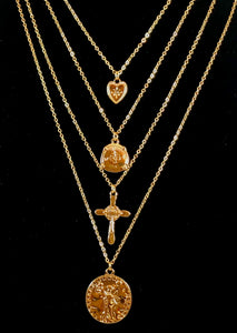 "Magnified image of the set of four gold necklaces that can be layered or worn separately. Set includes Heart Charm with Rhinestone North Star Necklace, Compass Charm Necklace, Cross Charm Necklace, and Coin Charm Necklace.  Approximately 16-18-20-22"" Length, with Clasp Closure with 3"" Ball Extension."