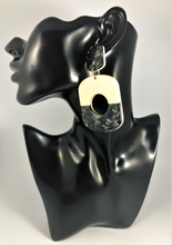 "Load image into Gallery viewer, Circular shaped marbled two color mod drop earrings in ivory and black. Approx. 3"" Length x 1.8"" Width, with post back."