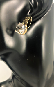 Magnified image of a clear cubic shaped stud on a gold post earring. It is a post back earring.