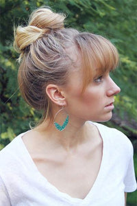 gold drop earrings with turquoise beads on model