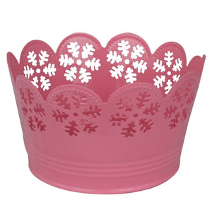 Pink metal bowl with snowflake cutouts and scalloped edges