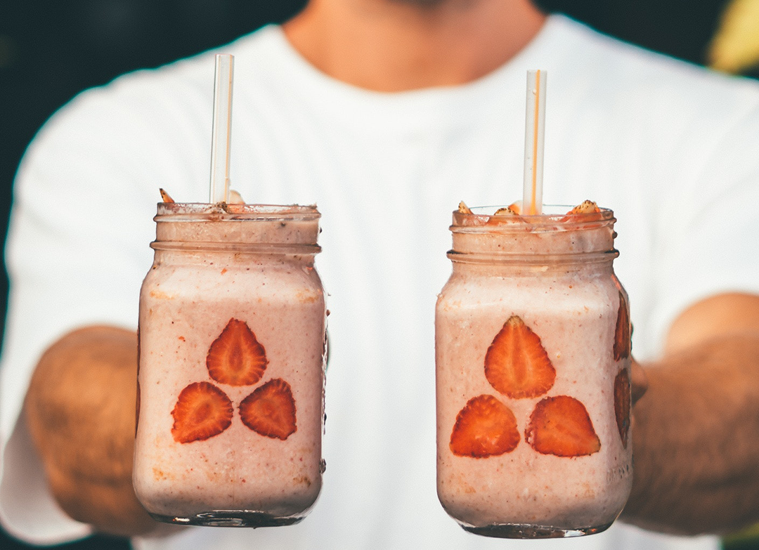 hands holding two smoothies with strawberries and sunbutter