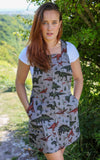 April Pearson in Grey twill Run and Fly Pinafore dungaree dress with dinosaurs