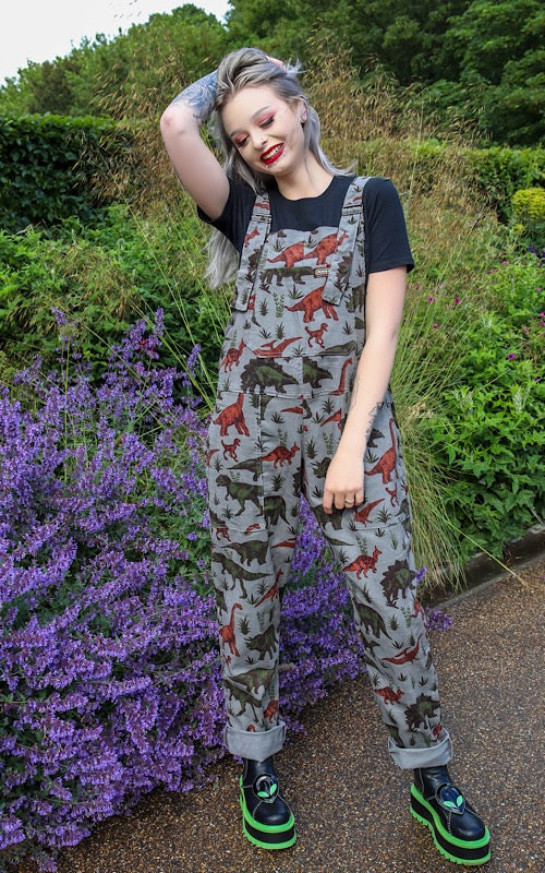 model storm kitty is smiling and wearing grey dinosaur dungarees with a black tee underneath and alien Koi Footwear vegan boots.