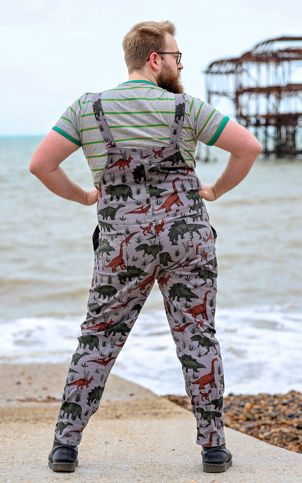 Man with a beard smiling by the West Pier in Brighton wearing grey dinosaur twill dungarees with a striped t-shirt underneath and black boots