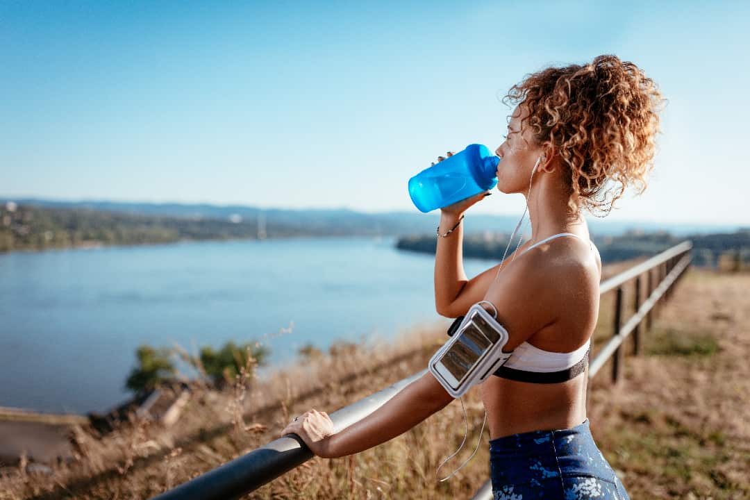 Woman Drinking Water with Magnesium During Exercise