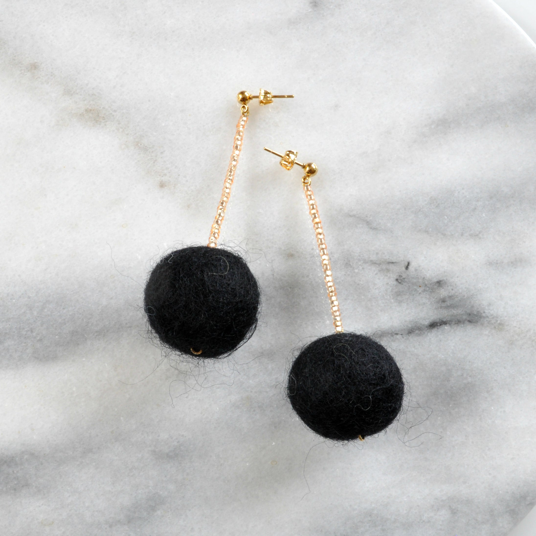 Libby & Smee pom pom earrings in Black with gold color combination