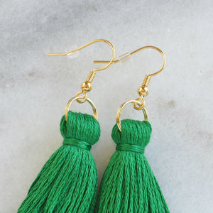 Close up of Emerald Green tassel earrings from Libby & Smee with a plastic earring backing