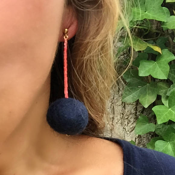 Libby & Smee pom pom earrings in Navy with neon coral color combination on model close up