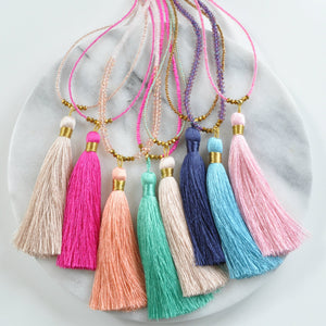 Libby & Smee champagne tassel necklace, with Libby & Smee beaded tassel necklaces in fuchsia, navy blue, aqua and pink