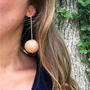Libby & Smee pom pom earrings in Blush color combination, close up on model