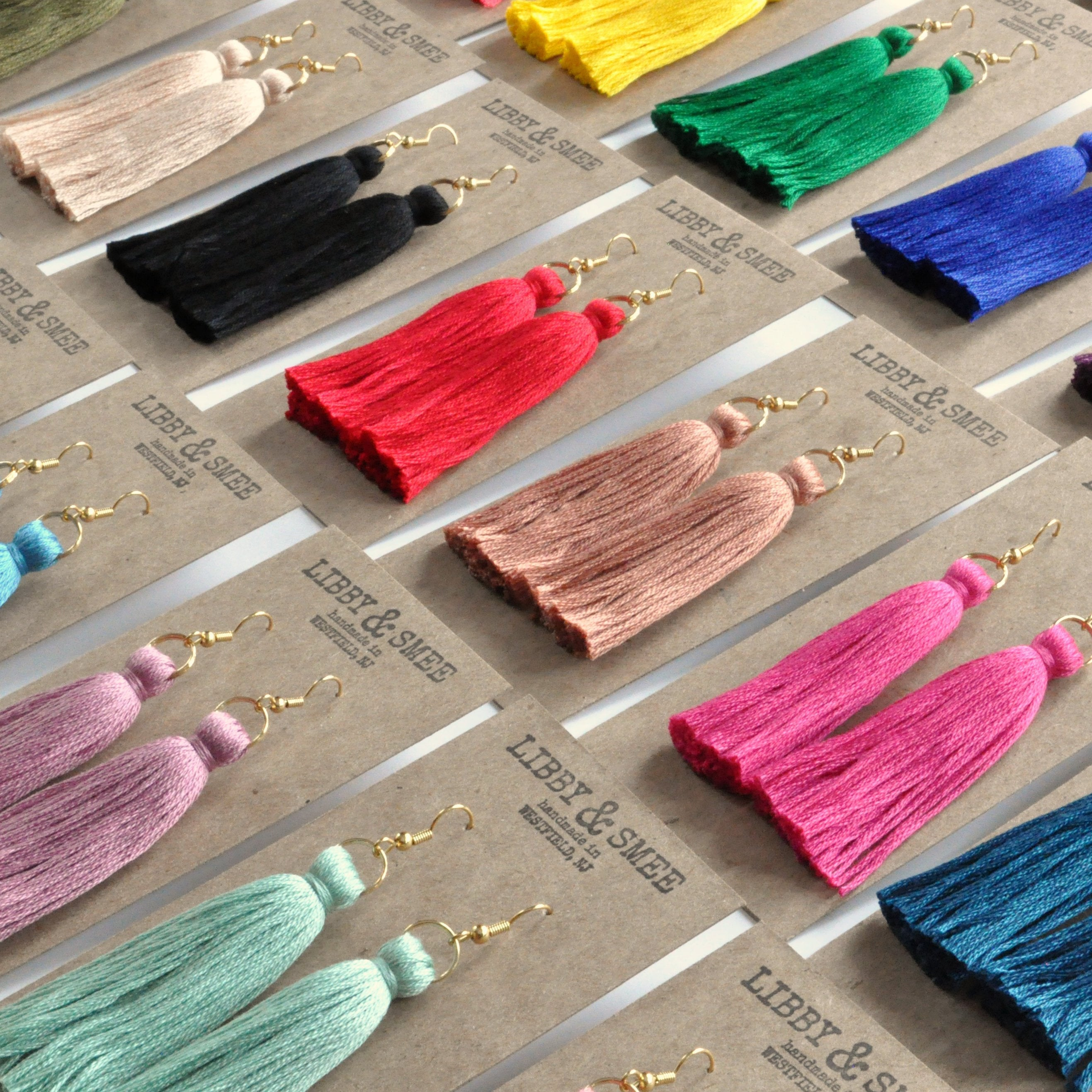 Libby & Smee Tassel Earrings side angle, several colors on kraft earring cards, still life