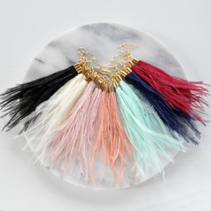 Libby & Smee Navy Blue Feather Earrings with Ostrich feathers and gold caps, still life with other ostrich feather earrings in black, ivory, pink, blush, seafoam, and red