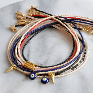 Libby & Smee beaded choker necklaces with small seed beads, gold spike accents and evil eye charms