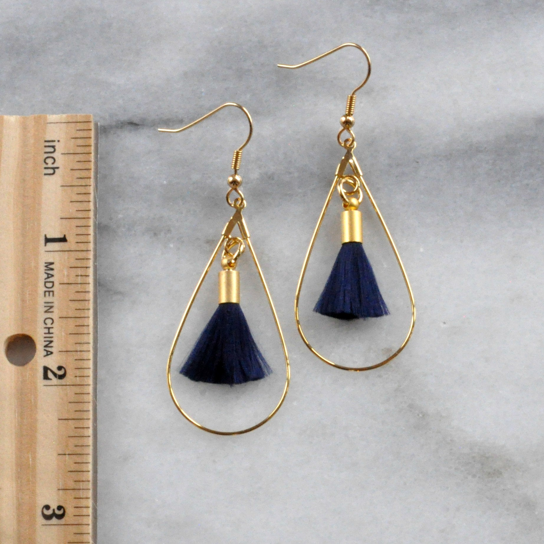 Libby & Smee tassel hoop earrings in Navy Blue in teadrop shape, still life with ruler for scale