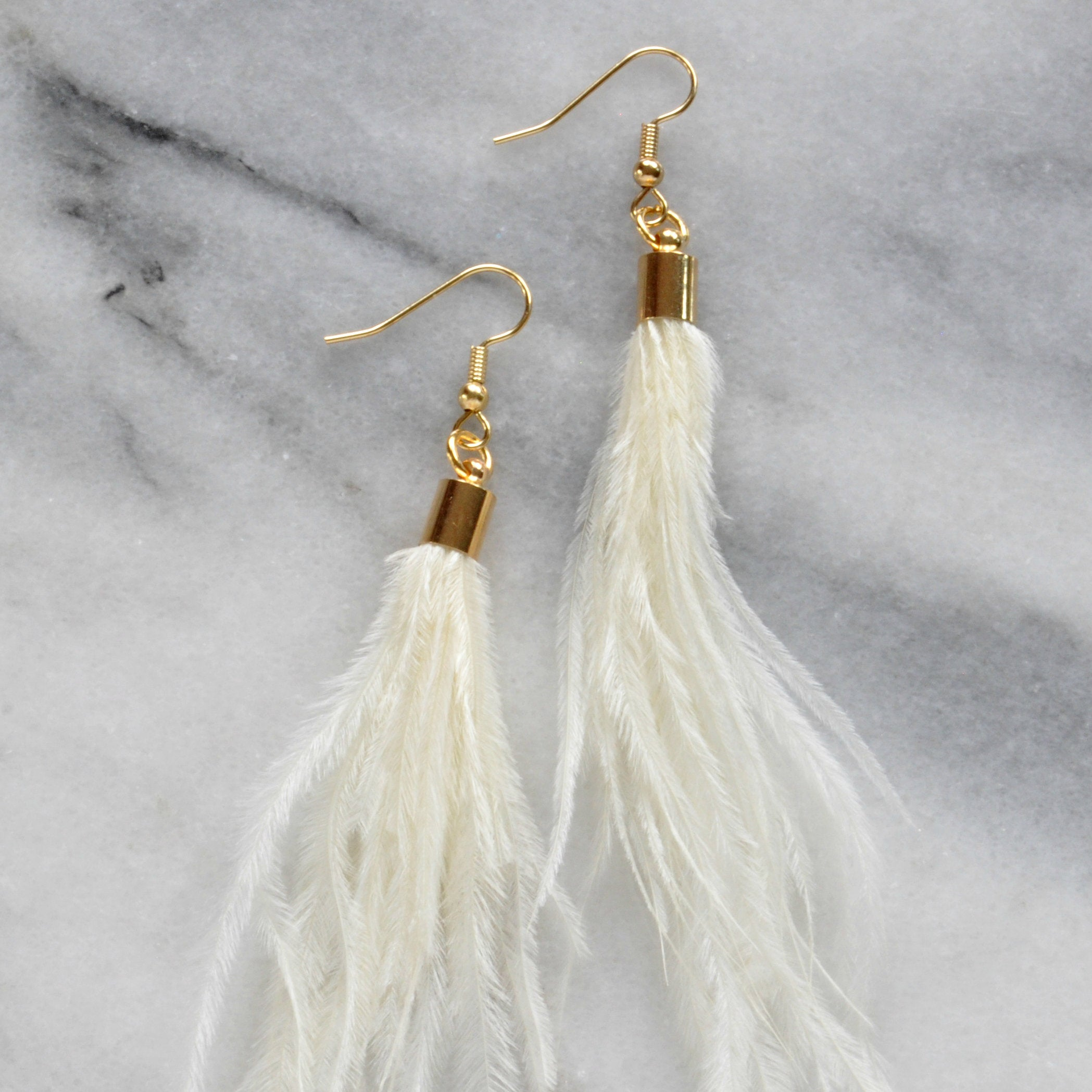 Libby & Smee ivory ostrich feather earrings with gold cap, still life on kraft logo earring card
