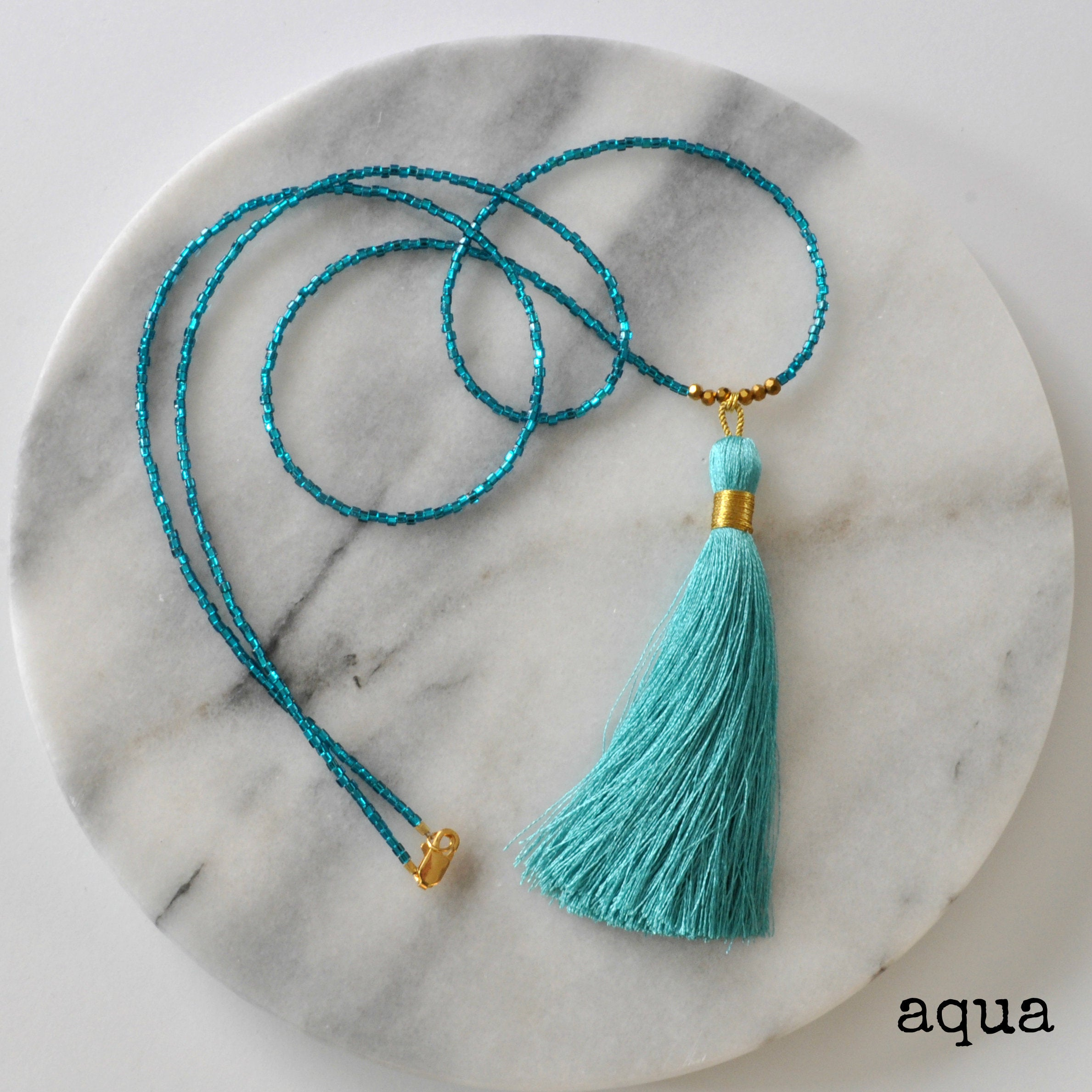 Libby & Smee Beaded Tassel Necklace in Aqua, still life labeled