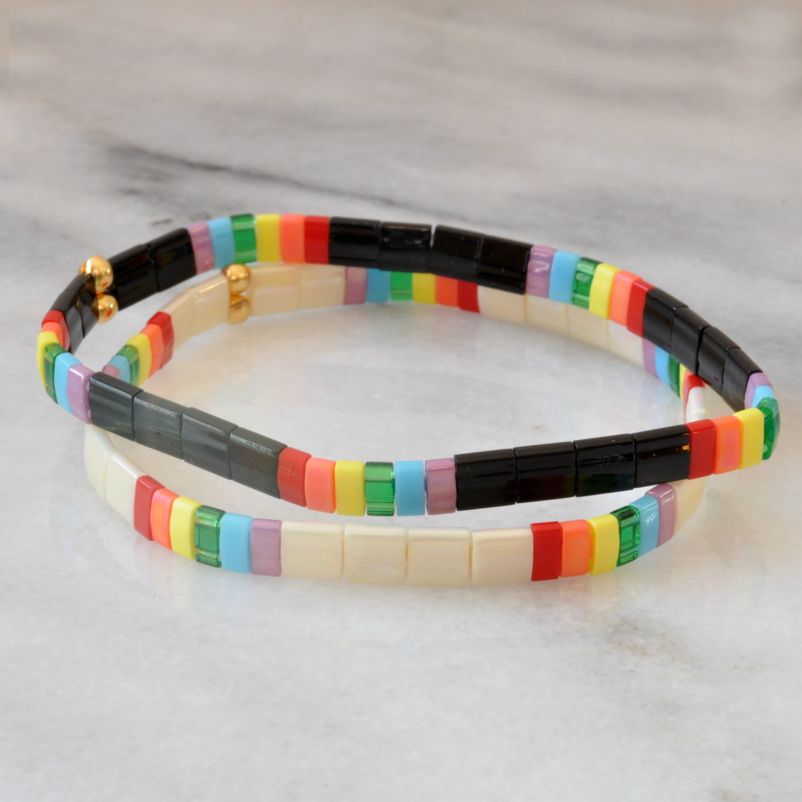 Libby & Smee Rainbow Stretch Bracelet in Ivory tile beads and in Black, still life