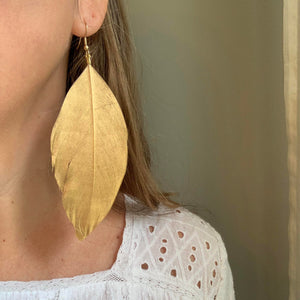 Libby & Smee 5 inch long gold feather earrings, on model