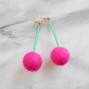 Libby & Smee pom pom earrings in Hot Pink with Green color combination, still life