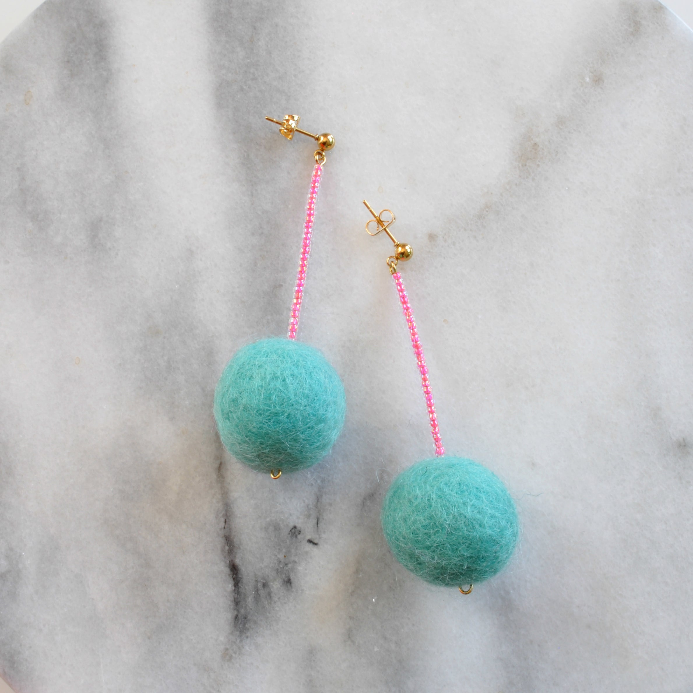 Libby & Smee pom pom earrings in Aqua with Neon Pink color  combination