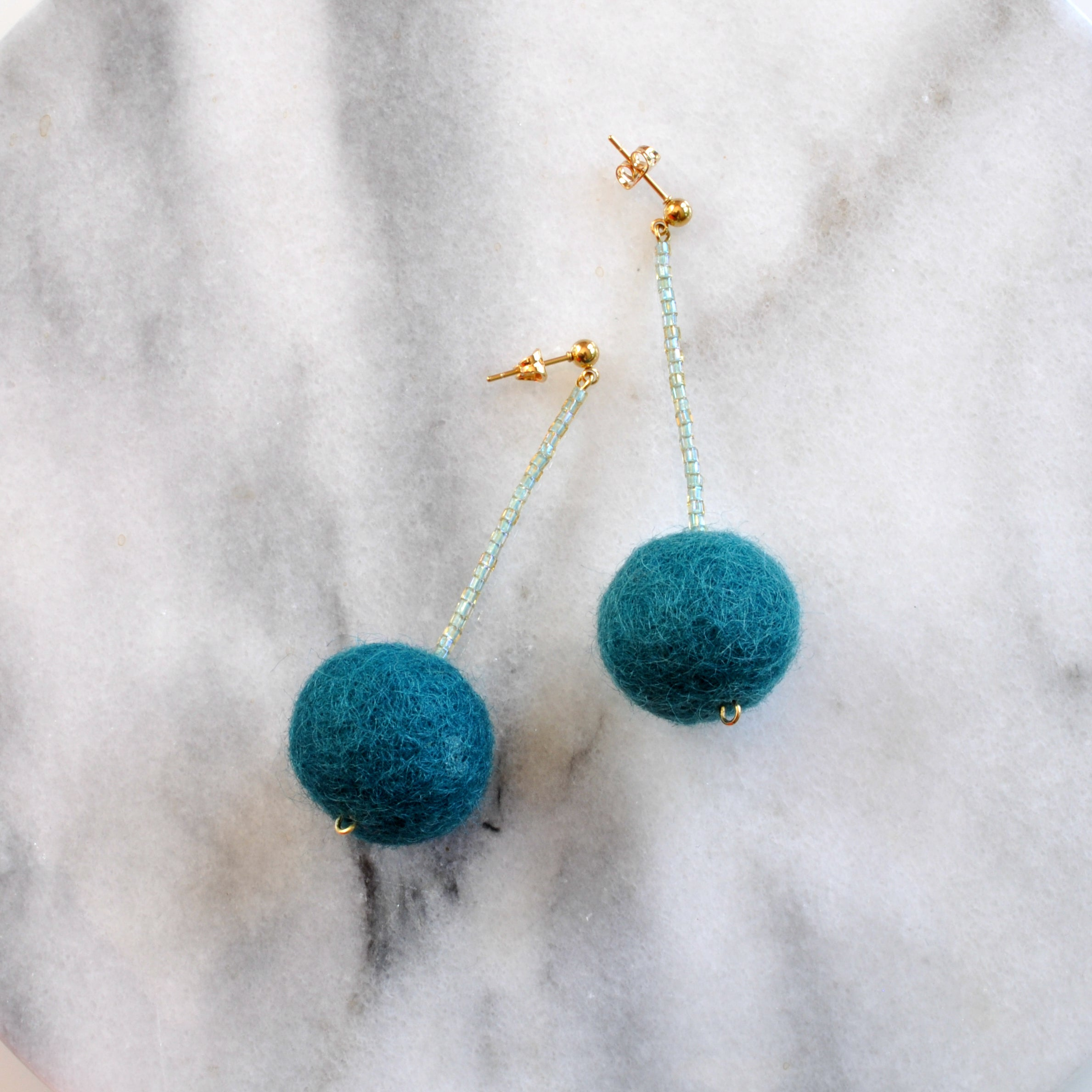 Libby & Smee pom pom earrings in Teal with seafoam color combination, still life