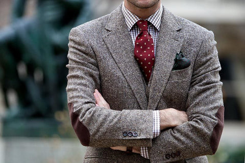 man in tweed jacket accented by pocket square