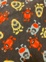 Flannel 2578- grey with yellow, orange, and blue happy monsters