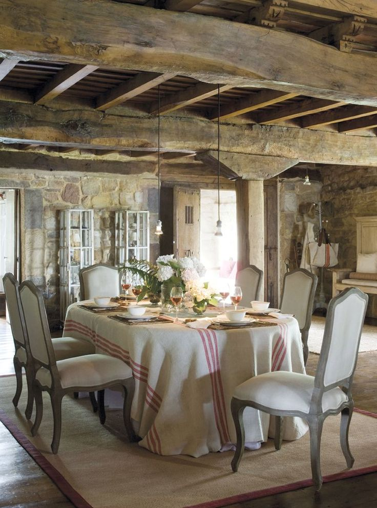 French Provence Chairs in old stone dining room with wood beams.