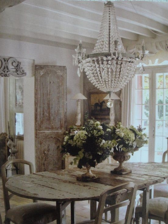 A heavily distressed dining room table serves as a rustic French country focal point.