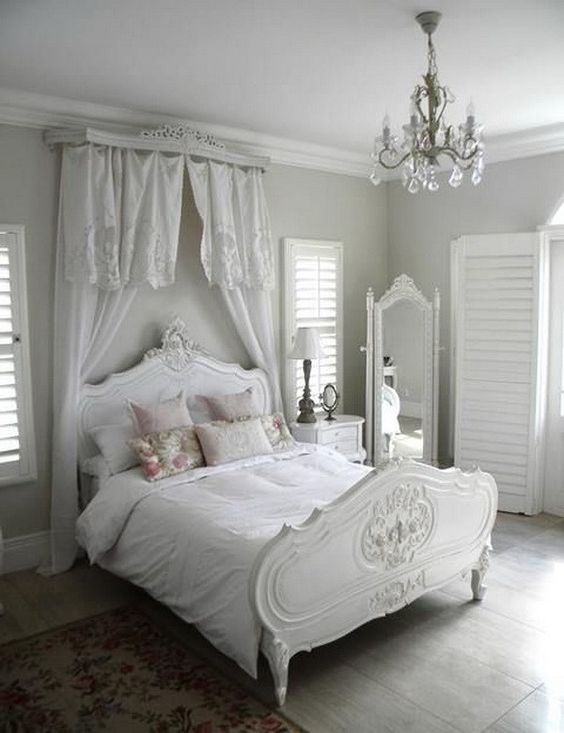 white shabby chic bedroom with crystal chandelier.