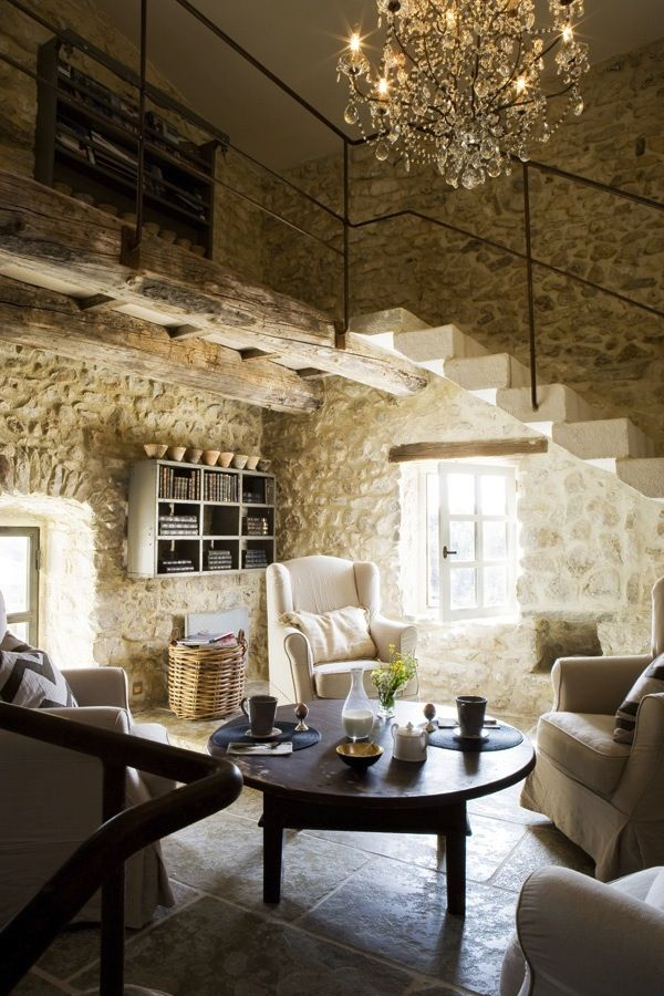 Love the contrast of the stone walls, the chandelier and the simple iron railing..