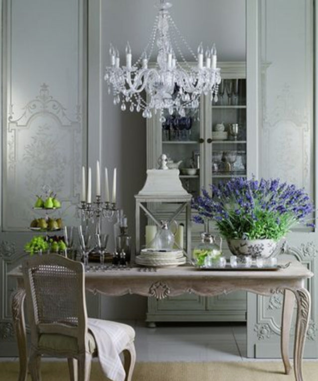 Curved Provincial dining table with cane chair and purple flowers