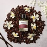 Joe Smooth perfume bottle on a bed of coffee beans surrounded by vanilla flowers
