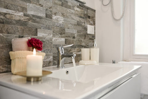A beautiful bathroom sink with backsplash and lit candles