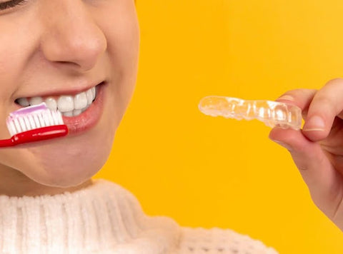 Close up of a young woman smiling while holding up a toothbrush and a mouth guard