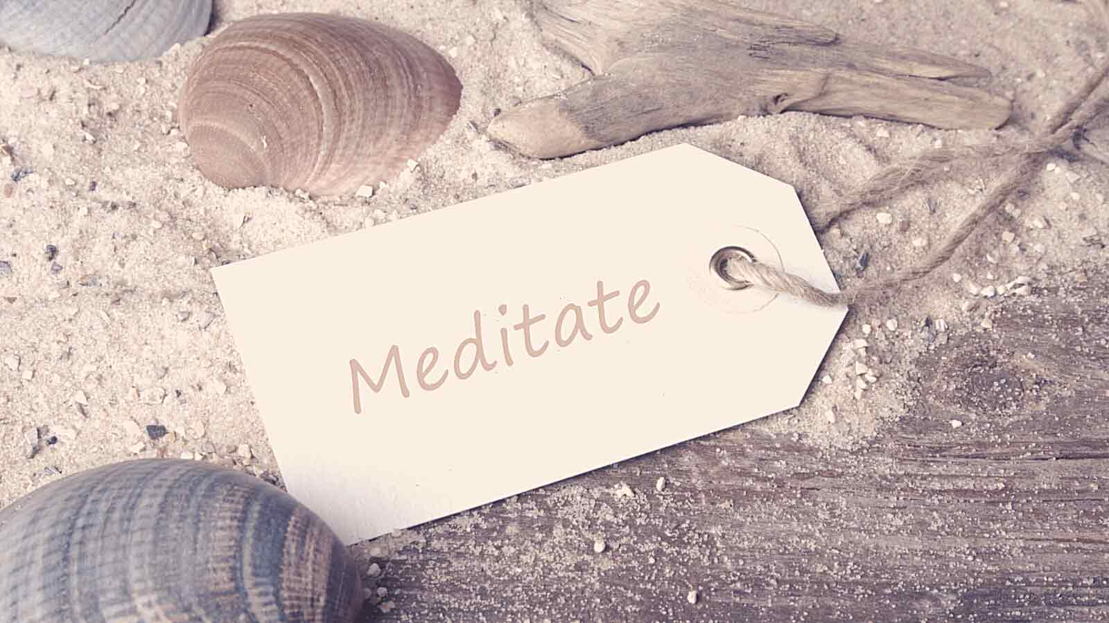 "The wooden tag, laying on the sand. ""Different types of meditation"" is engraved on the tag."