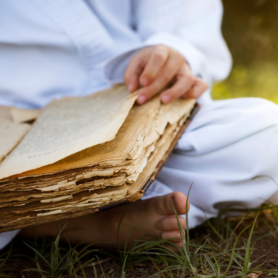 Meditation beginner is reading a book about history of meditation.