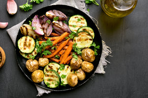 Image of a black plate sitting on a white cloth towel with frayed edges.  In the corner are two pieces of garlic and parsley.  On the plate are roasted vegetables: zucchini, new potatoes, and red onions around the outside with carrots sliced lenthwise in