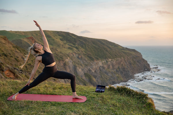 Woman practising yoga on top of a beautiful mountain on her Les Mills MBX mat