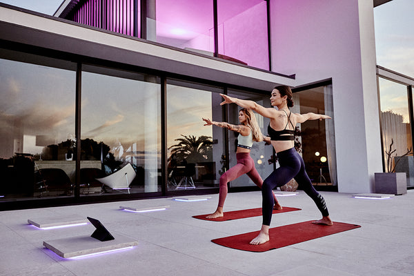 2 women practising yoga in their garden through a Les Mills Body Balance class. Both are on an MBX mat in the middle of a warrior pose